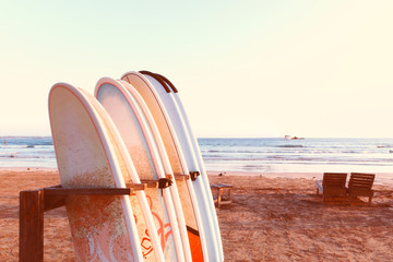 Vacation holidays background wallpaper - row of surfboards, two lounge chairs on beach. Concept of active exotic rest. Toned with Instagram filters. Empty place for text, copy space. Wall mural