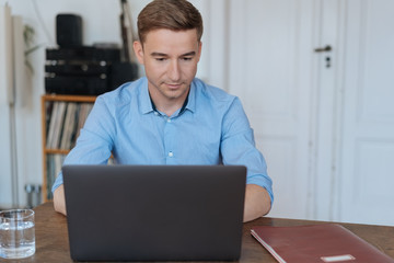 Man in blue shirt working on computer