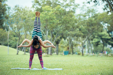 Beautiful fit Asian female base standing on stretch mat and bending forward holding on back female flyer with raised up legs, both elegantly holding hands on blurred background of park