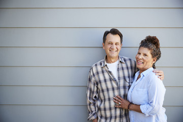Portrait Of Senior Couple Standing Outside Grey Clapboard House