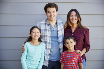 Portrait Of Happy Family Standing Outside Grey Clapboard House