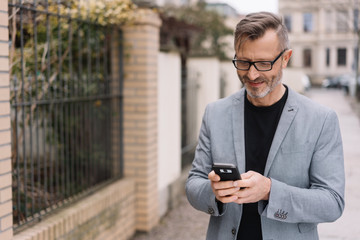 Mature, metro man happily texting in street scene