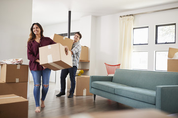 Excited Couple Carrying Boxes Into New Home On Moving Day