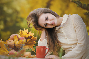 Young woman in the autumn park holds red tea cup