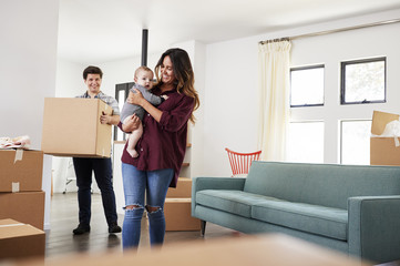 Family With Baby Carrying Boxes Into New Home On Moving Day