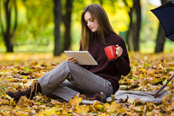 Pretty teenager girl  is  usind gudget sitting  on yellow autumn leaves on the ground in park and drinks tea
