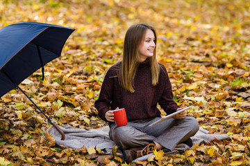Pretty teenager girl sits on yellow autumn leaves on the ground in park and drinks tea