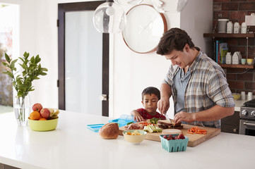 Father And Son Making School Lunch In Kitchen At Home