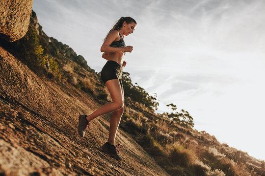 Woman trail runner training for down hill run