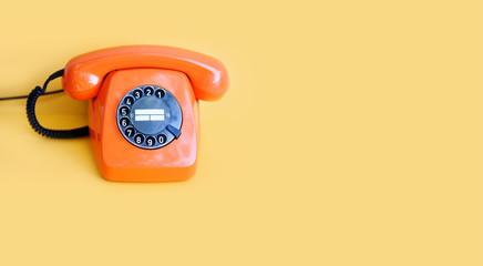 Retro phone orange color, vintage handset receiver on yellow background. copy space