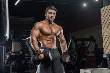 Young handsome male athlete bodybuilder, hard training in modern gym. Concept - personal trainer, strength, crossfit, styrodes, sports nutrition, diet, formology.