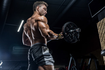 Foto auf AluDibond Fitness A young brutal male athlete is a bodybuilder with a perfect abs, exercising in the gym. Concept - strength, bodybuilding, styrodes, weightlifting, diet, muscles, sports nutrition, personal trainer