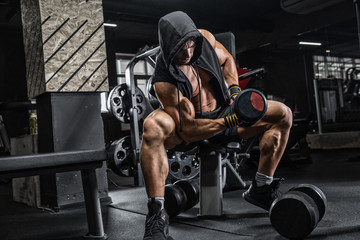 The brutal man is training the biceps on the bench, using a dumbbell. Concept - personal trainer, diet, sports nutrition, crossfit, styrodes, dumbbells, bodybuilding, weightlifting, gym.