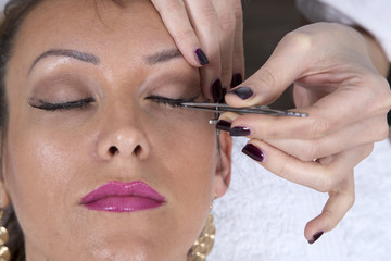 Closeup Of Young Woman's Face With Professional Makeup And Beautician's Hands Applying Fake Eyelashes, Top View