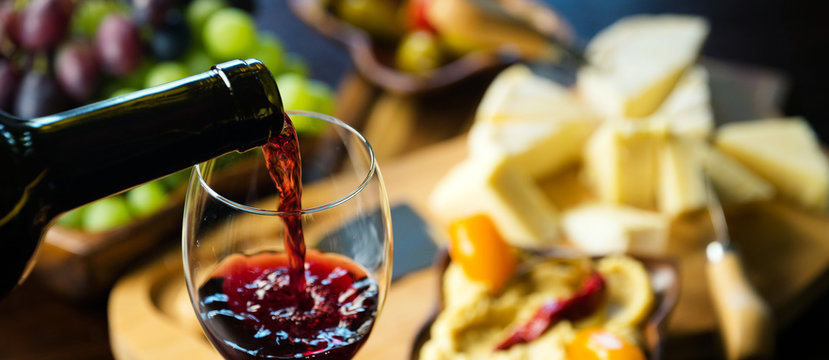 Pouring red wine into the glass in the background composition of appetizers