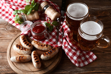 Mugs of delicious beer with grilled sausages and tomato sauce on wooden table