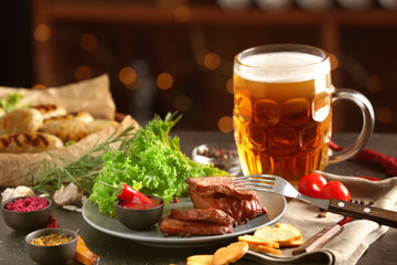 Mug of delicious beer with grilled steak and sauce on table