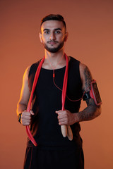 Handsome serious sportsman in headphones and armband holding jumping rope while looking at camera