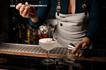 Bartender girl throwing ice to a white cocktail decorated with dried flowers