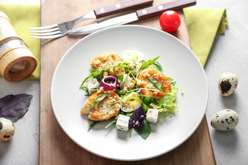 Plate with tasty chicken salad on wooden board