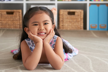 Portrait of cute smiling little girl lying on the floor at home