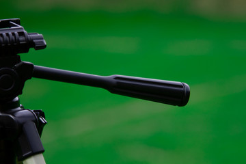 The head of the tripod for the camera is black on the background of a bright green lawn. Close-up photo.