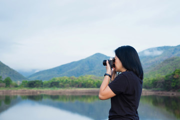 Young traveler woman backpacker use camera take a photo of beautiful of natural lake and mountain view,Freedom wanderlust concept.