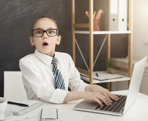 Shocked little girl working on laptop