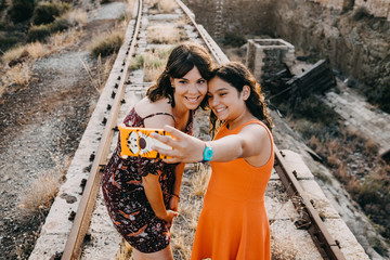 .Two young sisters enjoying a fun summer afternoon on abandoned train tracks, taking fun pictures together. Family vacation. Lifestyle.