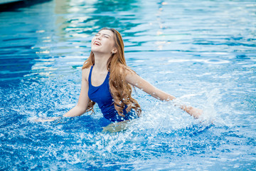 Beautiful young asian woman smiling in a swimming pool splashing water . Happy lady girl sexy  laughing in swimsuit playing having fun in the pool