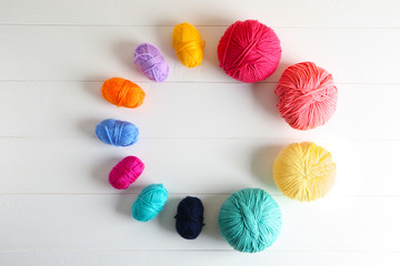 Composition with different knitting yarn on white wooden background