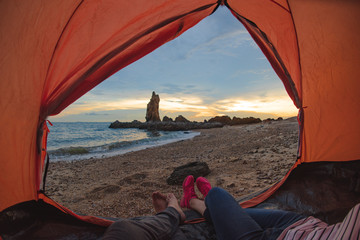 legs of couple lover laying out of the tent to the sea beach at morning sunrise with wonder landscape thick of stone in background