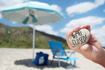 man on the beach and text we are closed