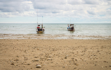 Two traditional Thai fishing boat anchored on a beach. Seascape view of Andaman sea from Thailand.