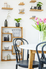 Close-up of a black chair and white table with tulips, and decorated shelves in the background