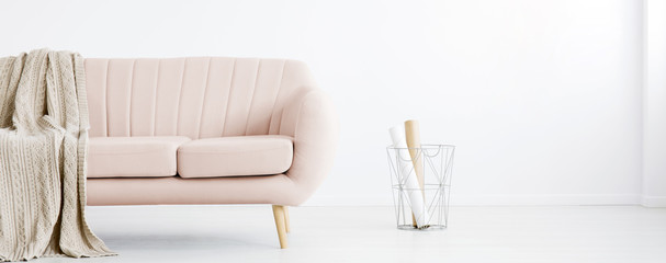 Real photo of white living room interior with metal basket with paper rolls and pastel pink couch with coverlet