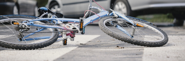 Close-up of a bicycle on an empty road crossing with cars in the background - a dangerous car accident concept