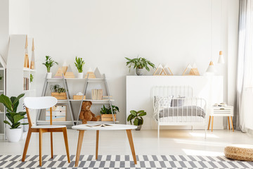 Wooden chair and table with open book placed on carpet in real photo of bright Scandinavian style bedroom interior for teenager with metal bed, fresh plants and triangle racks