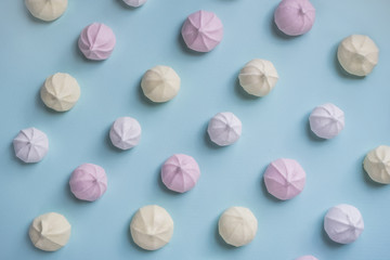 Colorful food pattern of pink, yellow and white meringues on blue background. Top view. Flat lay