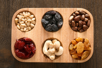 Wooden board with dried fruits and nuts on table, top view