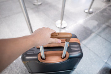 Traveler hand holding suitcase in an airport.