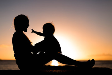 Mother and child playing and watching sunset on the beach in silhouette