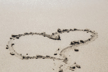 Love sign writing on sand. Heart on a sand