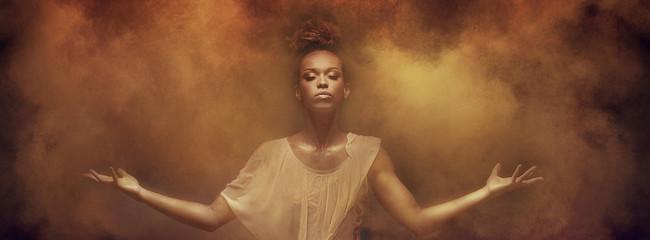 Beautiful afro girl dancer over dust.