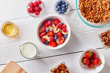 Ingredirnts for preparing healthy organic breakfast - granola, berries honey, milk, banana in white bowl on white table. Flat lay.