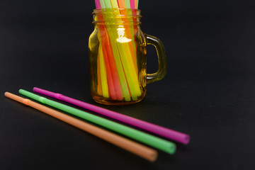 Bright colorful party drink straws in jar and lines .
