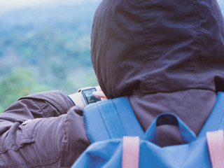 backpack and camping concept from woman in warm cloth with her bag during check heart rate by her smart watch after travel and walk to mountain in morning after sunrise