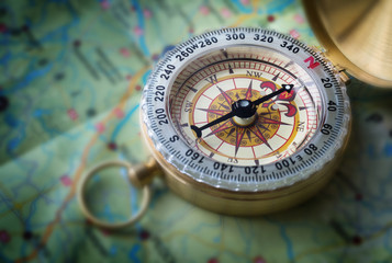 Wall Mural - Magnetic compass on world map.Travel, geography, navigation, tourism and exploration concept background. Macro photo. Very shallow focus.