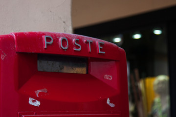Detail of an Italian red mailbox in a column with the word Poste and shabby stickers on it. Italy. Europe. No people.
