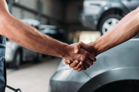 cropped view of mechanics shaking hands in auto repair shop